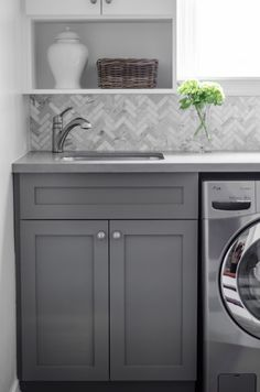 Laundry room with herringbone tile backsplash, herringbone tiles, (calcutta marble herringbone tiles) Laundry Mud Room, Interior, Marble Herringbone Tile, Laundry Room Inspiration, House Interior, Herringbone Tile, Grey Cabinets, Trending Decor, Laundry