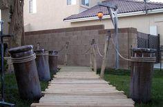 Pallet walkway through yard. Cardboard tubes painted to look like weathered wood.
