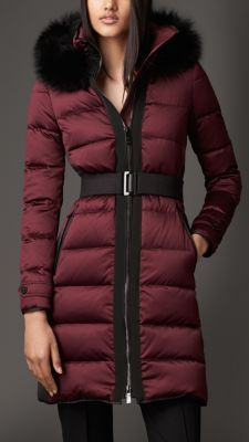 A down-filled puffer coat with a detachable fox fur trim at the hood. The coat is constructed from a woven technical fabric with a showerproof coating and a lustrous finish. Stretch rib-stitch side panels and a belted waist give a contoured, feminine fit. Grosgrain taping at the zip adds definition and texture to the piece.
