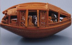 """Carved Olive Pit in the National Palace Museum in Taipei.    Ch'en Tsu-chang (a minor official) followed the natural shape of an olive pit to carve a small boat and based his carving on Su Shih """"Latter Ode on the Red Cliff"""" is carved on the bottom of the pit (not shown here). On the boat are eight figures, each of which is animated and expressive."""