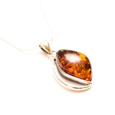 """This cute design features a subtle cognac Amber stone surrounded by a modern and wavy sterling silver design. A beautiful, smaller necklace - perfect for all occasions.The Amber stone has been sculpted for centuries by the everlasting waves of the Baltic Sea, and are hand picked just off the shores of Poland. The necklace includes a 17.5"""" (45cm) sterling silver snake chain."""