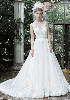 This exquisite ball gown wedding dress is complete with floral lace appliqués drifting down a tulle skirt, an elegant illusion V-neckline, and a glittering Swarovski crystal belt. Finished with plunging V-back and crystal buttons over zipper closure.