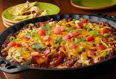 Grab a chip and dig into thissimple dip that's really delicious. Cream, cheese, salsa, chili and Cheddar cheese are layered and baked until hot and bubbling. Top it with green onion, tomato and fresh cilantro for a tasty dip that is sure to be a hit.