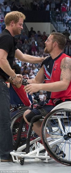 It starts with a formal handshake a pat on the shoulder but Prince Harry is soon pulled into a hug by the member of the member of GB's wheelchair basketball team