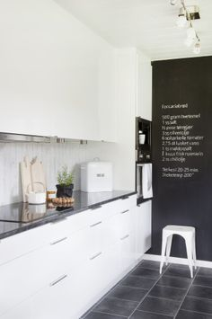 Stark white contemporary kitchen with metal stools and a chalk board.
