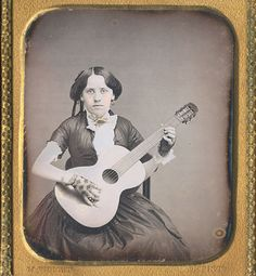 "Sixth plate daguerreotype of a woman playing her guitar, with mat stamp for ""M. WRIGHT / ARTIST""."