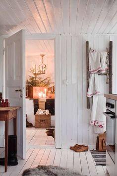 """En gammal stege fungerar som handdukshängare i köket. I matrummet sprider mängder av tända ljus varm julstämning. """"Rött har ju i sig en betydelse och associeras med styrka, kraft och beslutsamhet. Men den är också kärlekens och julens färg"""", säger Susan som är trädgårdsmästare och självlärd stylist."""