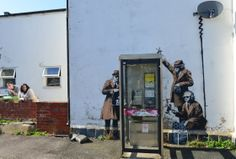 Suspected Banksy artwork appears on the side of a house, depicting government agents spying on a phone box near GCHQ (Government Communicati...