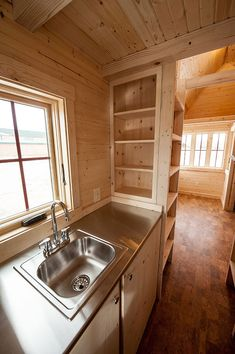 stainless steel sink/countertop... built-in storage shelves divide kitchen from main room ~ colorado fencl, tumbleweed tiny house company