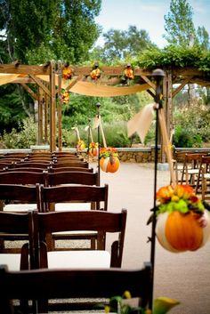 Like hollowed pumpkins with flowers for aisle decor