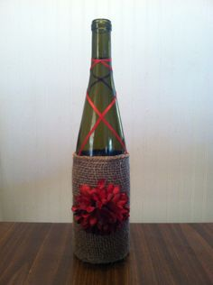 Green wine bottle with red ribbon, red flower and burlap