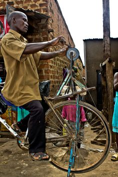 Africa |  Knives sharpener, Katwe, Uganda - Photography by Edward Kimbowa