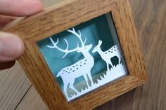 This cute mini reindeer paper cut design is designed and cut by paper petal.  Framed in a handmade oak frame, it features two wondering deers in a glittery forest. Price: £26