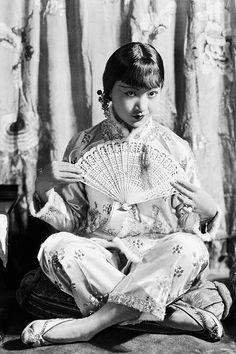 Anna May Wong sitting cross-legged, 1930.