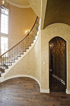 Circular staircase with wine nook (or whatever... maybe a vintage phone booth) underneath and rounded ceiling under stairs.