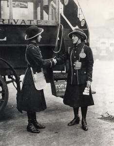 Two the First World War women conductors shaking hands beside the rear of a bus.    Unknown photographer, 1916 - 1919
