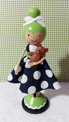 Alexis, a super cute wooden clothespin doll stands just over four inches tall, and is uniquely hand painted in vibrant colors and wears a real cotton fabric dress in a navy blue and white polka dot print.