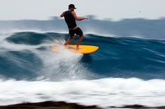Chris Malloy surfing on an orange surfboard in the Mentawaiis in Indonesia, photographed for Patagonia by Jeff Johnson