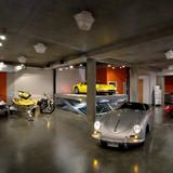 Underneath this waterfront home, a James Bond-style subterranean garage hosts multiple vehicles. The cement floor, bold color and industrial details showcase the home's contemporary design.