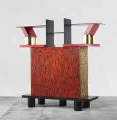 ETTORE SOTTSASS    Freemont cabinet    Memphis  Italy, 1985  plywood, laminate over wood, gilt and lacquered wood  76 w x 24 d x 72 h inches  Cabinet features two doors concealing two adjustable shelves. Signed with applied manufacturer's mark to shelf: [Memphis Milano Ettore Sottsass 1985 Made in Italy].