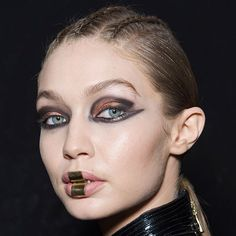 """That's not makeup"" #TomPecheux told our digital deputy beauty director @spanych. ""It's a piece of jewelry created by Olivier that's why we're only putting balm on the lips.""  The #MUA also created a black-and-metallic eye look that required him to pull out all the stops: black pencil black gel liner two loose metallic pigments and black eye shadowmore makeup than any previous #Balmain runway show. Click the link in our bio for 6 more details about the look that you need to know…"