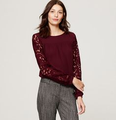 Rib knit cuffs and a relaxed silhouette add a clever sweatshirt-inspired whisper to this lace sleeved lovely. Ballet neck. Long sleeves. Front and back yoke. Keyhole at back neck with button and loop closure. Shirred beneath front and back yoke. Shirttail hem.