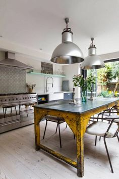 sol en planchers beiges, table en bois peint de couleur jaune, lustres argentes