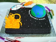 """Outer Space Birthday - This was for my friend's little boy's 5th birthday.  The cake is iced in buttercream, then covered with black sugar. The """"world"""" is half a ball pan cake covered in fondant.  My husband cut out the continents. The space ship, stars and sun are colorflow, which I made using templates that my husband drew."""