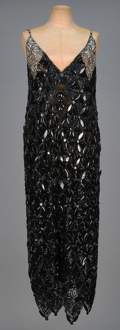SEQUINED TULLE EVENING TABARD with RHINESTONES, c. 1923. Sleeveless black V-neck with an allover lattice of black paillettes on a black sequined ground, the shoulder decorated in marquise and round rhinestones with silver sequins, jeweled narrow strap, four large hem points having faceted paillettes and beads. Front