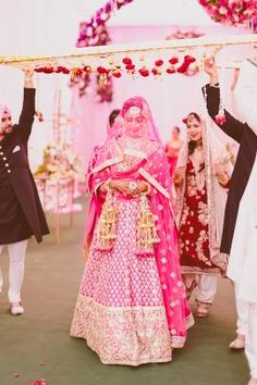 Indian Wedding Photography - The entrance of the bride, with the floral canopy carried by the brothers. Captured by: Arjun's Tryst With The Camera.  Get inspired by more wedding photography on wedmegood.com. #wedmegood #wedding #photography
