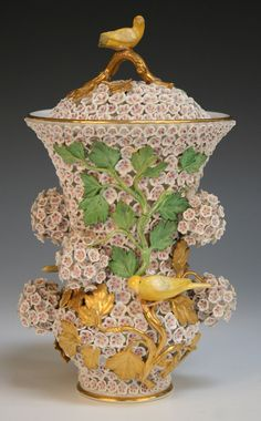 A Meissen porcelain Schneeballen vase and cover with gilt handle and canary finial, late 19th/early 20th Century, the flared neck and low bellied body encrusted with white flowers and applied with gilt and green leaves with opposing canaries perched on them, underglaze blue crossed swords to base, incised numerals 2750, impressed '46' and '20', gilt painted '30', height approx 20cm