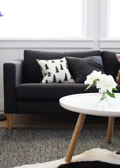 http://www.amerrymishapblog.com - dark gray karlstad, slightly lighter gray rug, wood floor, pops of white and color