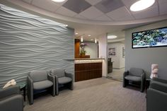 The waiting area introduces the sophisticated ocean theme, with a soft teal feature 'wave wall'. Chair upholstery is completed in a pattern just a shades deeper than the walls to create the illusion of a larger space. A surround sound system plays ethereal sounds while a 'virtual' fish tank changes view on the TV monitor. The reception desk is enhanced with LED enhanced blue-green mosaic glass. Accent pendants, and round porthole ceiling lighting complete the theme.
