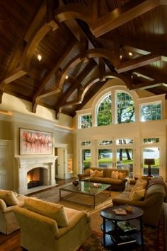 Wooden arched beams shape match the arched large window nicely. Warm room colors and soft seating make for a very comfortable living room.