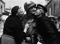 An American soldier is welcomed with kisses after the liberation of St. Saveur village from German control. August 8, 1944