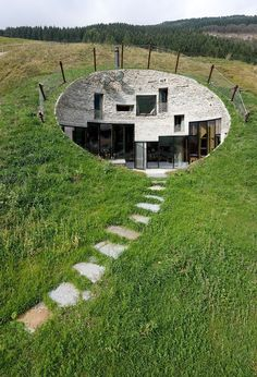 A house in an Alpine slope. Underground houses have always been a fascination to me. Theres something about them that is really cool, but really terrifying as well. This one is beautiful. The white against the green is lovely and the stepping stones are to die for.