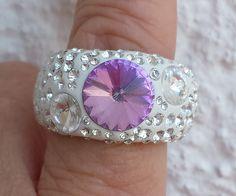 Bei diesem Edelstahl-Ring ist das Highlight der große Kristall in der Ringmitte in der Farbe Vitrail light, der von zwei kleineren klaren Kristallen und vielen