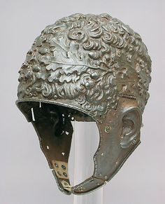 Helmet all'antica  Attributed to Filippo Negroli (Italian, Milan, ca. 1510–1579)  Date: ca. 1532–35   Fashioned as a head of tightly curled hair encircled by a wreath of oak leaves, this helmet evokes the appearance of an ancient hero, perhaps a Roman emperor. The reference to the oak (rovere, in Italian) may indicate that the helmet was made for a member of the della Rovere family, dukes of Urbino. The cheekpieces are probably nineteenth-century restorations.
