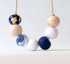 This navy, pink and gold beaded necklace is carefully handmade from polymer clay. It features seven beads including two with gold foiling and two marbled beads in blue and pink. It is finished with gold end beads and a feather charm at the end. The beads are strung on natural coloured leather cord and the necklace measures approximately 80cm in length. Each bead is carefully hand rolled and will therefore have slight variations in size, shape and finish, which ensures each necklace is…