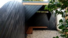 Black Larch & Iroko Outdoor shelter with a stunning hand carved bench by we make our way.