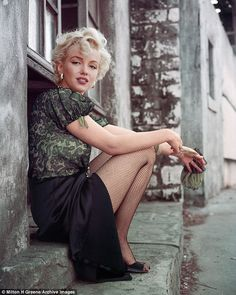 Marilyn wears fishnet tights and a green lace top in 'The Hooker Sitting', taken in Los Angeles in 1956