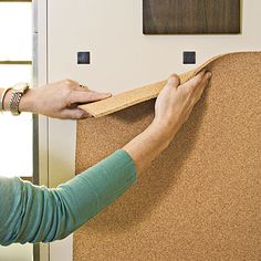 Install corkboard    Remove the painters tape one piece at a time, placing foam mounting squares at the corners and along the lines where the tape used to be. Gently place the cork in the space that you've defined. Check that it is level, and then press firmly, securing it to the wall. Repeat with the magnetic boards, adding tack nails to the top corners to support the weight.