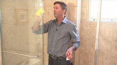 Cleaning Gl Shower Door Using Lemon Oil With Yellow Napkins
