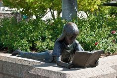 "Under a tree in front of the Pleasanton Library, a bronze statue of a young girl reading a book welcomes visitors. Under the statue, a small plaque credits the artist Dennis Smith and dedicates it to the ""Children of Pleasanton in Memory of Sarah Anne Lees."""
