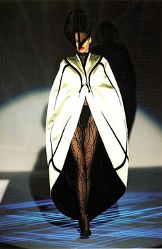 Diana Gartner wears a cocoon cape of pale green satin lined with black velvet, over a 'Dragonfly' bodystocking in black flocked net, with a 'Fly' hat in black velvet and horsehair.    Thierry Mugler  'Les Insectes'  Couture Collection  Spring/Summer 1997  Photo by Patrice Stable