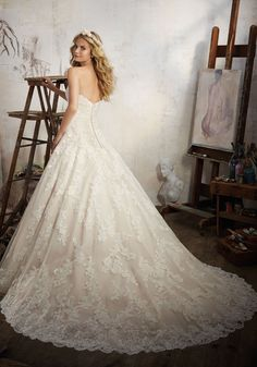 Alençon Lace AppliquŽés Accent this Classic Bridal Gown. Featuring a Strapless, Sweetheart Neckline and Tulle Ball Gown Skirt with Wide Scalloped Hemline.