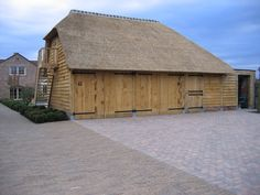 Eiken garage met berging en een verdieping. Voorzien van een rieten dak, aangebouwd tegen een bestaande woning.