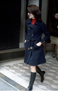Jackie shopping at Bonwit Teller (NYC) wearing navy double-breasted coat, red striped polo neck jumper, go-go boots and trademark oversize sunglasses. (1970)