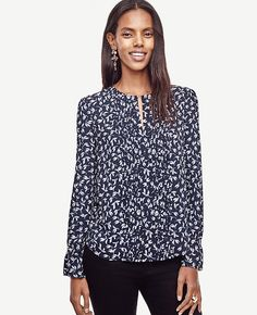"Finished with a sleek split neck, polished pintucks and ruffle cuffs, this leafy blouse is a modern romantic. Split neck. Long sleeves with shirred sleeve caps and shirred ruffle cuffs. Back yoke. Shirttail hem. 26"" long."