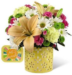 """Send a warm ray of sunshine and your happiest thoughts straight to their door with The FTD¨ Brighter Than Brightª Bouquet by Hallmark! Bringing together an inspiring collection of blooms, including yellow roses, peach Asiatic Lilies, yellow carnations, white daisies, green button poms, and hot pink mini carnations, this gorgeous flower arrangement is styled in a keepsake yellow ceramic vase, fashioned with a sweet cut-out design, and arrives with a Hallmark tag that reads, """"Hello Sunshine."""""""